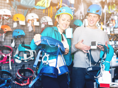Girl and the guy choosing in the shop of sports equipment a mountaineering equipment. Focus on woman