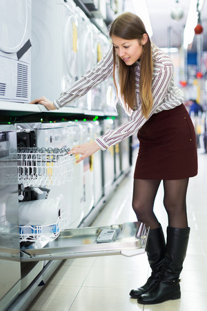 Positive girl looking for functional dish washer in store of consumer electronics