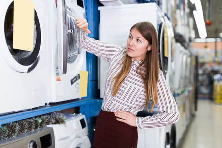 Glad female housewife choosing new washer in domestic appliances section Stock Photo