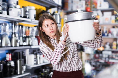 Positive girl looking for new slow cooker in section of kitchen appliances Stock Photo