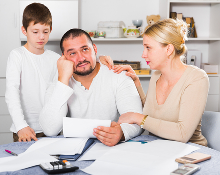 Loving wife with son comforting upset man at home table