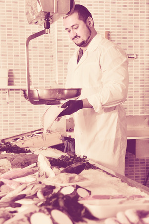 Positive man in glove behind counter shows fish in his hand Stock Photo