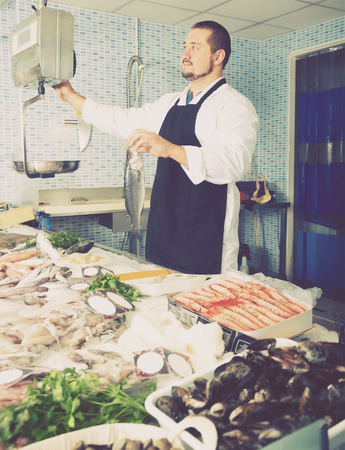 Seller in black apron holding fish and looking at scales in the shop Standard-Bild