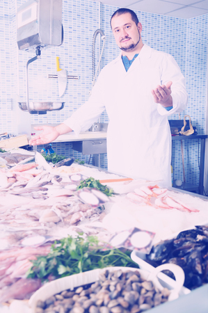 Adult polite man with beard arms folded standing near fish counter