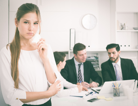 Unhappy and crying woman standing at office on background with coworkers Stock Photo