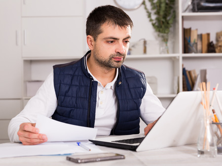 Young businessman in shirt working with laptopt and documents at the table