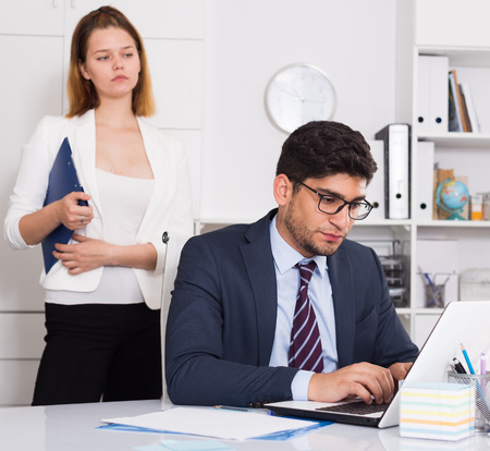 Upset man sitting at laptop with disgruntled female boss behind