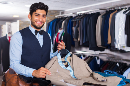 Male client demonstrating his choice of suit in apparel shop Stock Photo