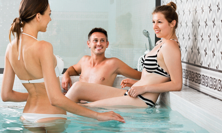 Three cheerful positive friends relaxing at spa, enjoying company