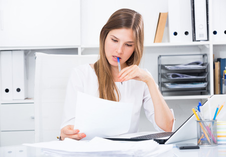 Upset young businesswoman working with documents in office