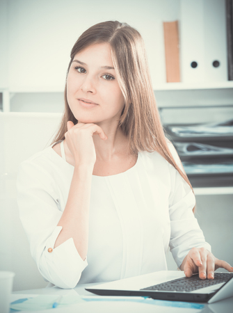 Happy young female entrepreneur sitting in office