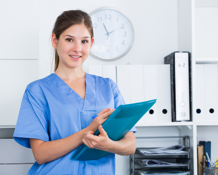 Smiling young female doctor writing notes on clipboard in clinic