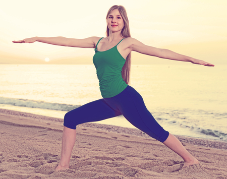 Female 20-25 years old is doing excercises on endurance on the beach near sea. Imagens - 94111849