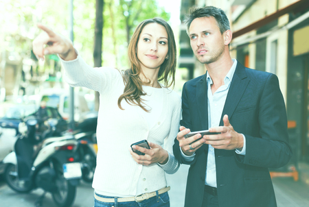 Guy and girl strolling through city streets and pointing each other something  Stock Photo
