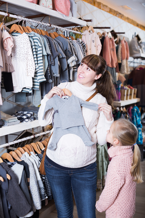 Glad pregnant mother and daughter examining romper suits for baby in children's cloths shop