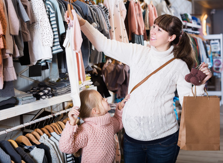 Cheerful pregnant mother and daughter examining romper suits for baby in children's cloths store Stock Photo