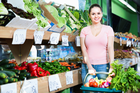 Portrait of cheerful positive smiling female purchaser holding shopping basket with fruits and vegetables Stock Photo