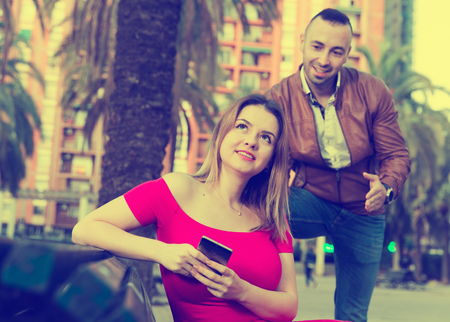 Girl is sitting with phone and inaccessibility for stranger man outdoors. Stock Photo