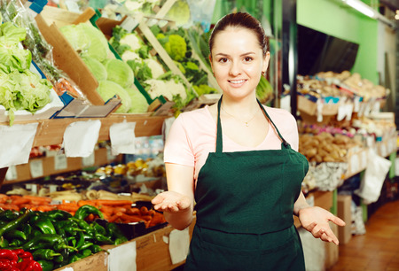 Positive young female grocery worker welcoming to a vegetable store Stok Fotoğraf