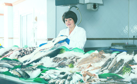 Adult woman selling chilled fish and seafood in store