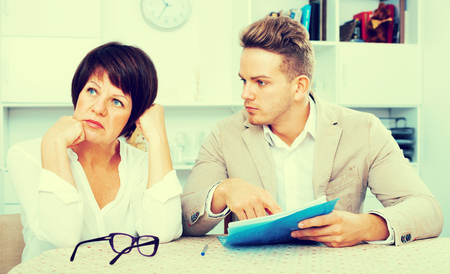 Mature mother was upset and has turned away from the son who suggests her to sign documents  Stock Photo