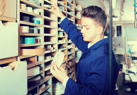 Young smiling european guy choosing strips to end edgings at workshop