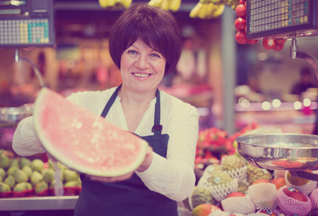 Mature woman offering watermelon and other fresh fruits on the market Stock fotó