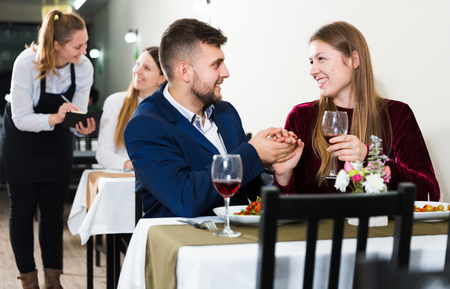 Elegant female and her boyfriend are celebrating date for dinner in luxury restaurante indoor. Banco de Imagens