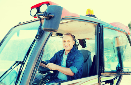 Portrait of diligent  male farmer in the special car at the cow farm.