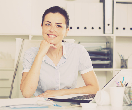 Cheerful businesswoman in shirt working at the computer in the office