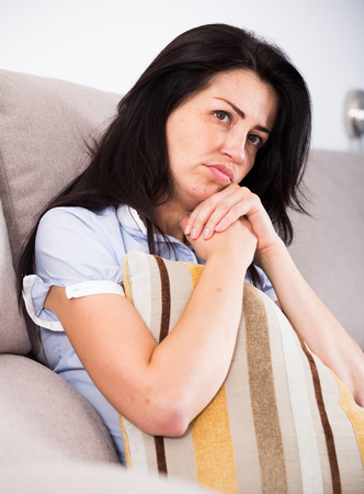 Adult sad female sitting on cozy sofa and melancholy with pillow