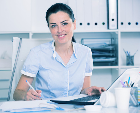 Portrait of adult female in the office sitting at the table