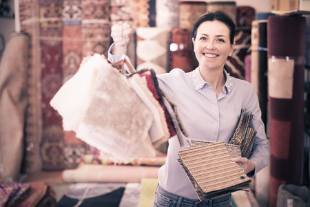Happy woman shopping carpet and showing samples in interior store