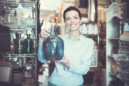 adults woman chooses glass decorative bottles at the local interior store