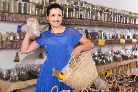 positive french adult  female choosing natural dried herbs sold by weight in eco shop