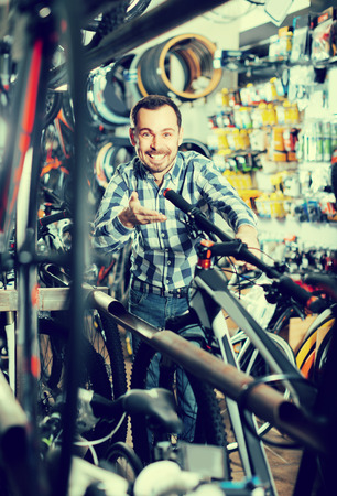 Biker is looking for bicycle handlebars in sports shop.  Stock Photo