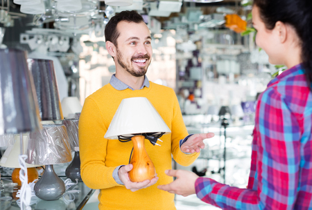 smiling man and girl in lighter shop choosing stylish and modern lamp for house interior