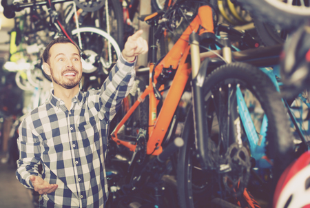Young positive man points to interesting details of bicycle in bike shop