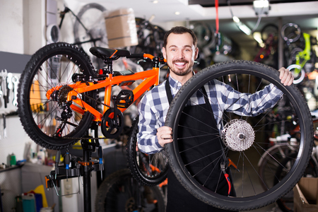 Smiling man in apron considering composition of wheel for bicycle