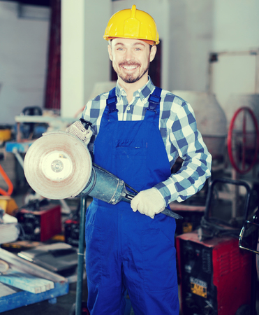 Young male worker starting to assemble with scaffoldings at workshop Stock Photo