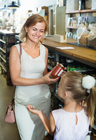 Portrait of smiling woman and girl buying conserve tomato sauce in glass jar in grocery shop