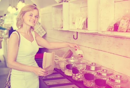 Cheerful female customer choosing nuts from glass jars in food shop