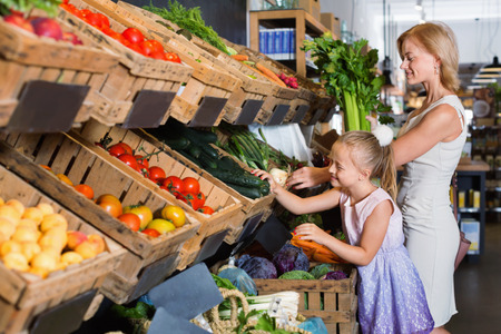 Glad positive young mother with smiling daughter shopping various veggies in food store
