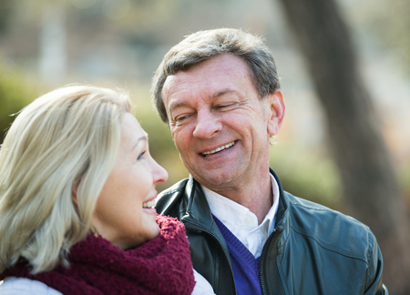 Smiling mature couple having flirting conversation in park