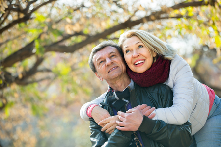 Portrait of romantic mature couple cuddling in park and laughing