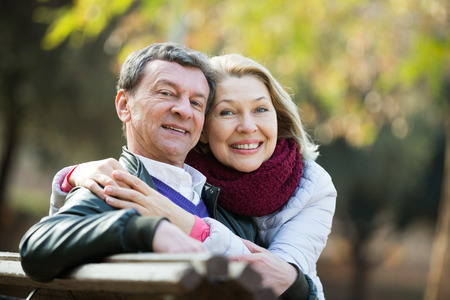 Happy pensioners cuddling in park and enjoying time together Stock Photo
