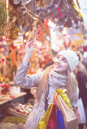 Happy smiling girl choosing Christmas decoration at market in night time