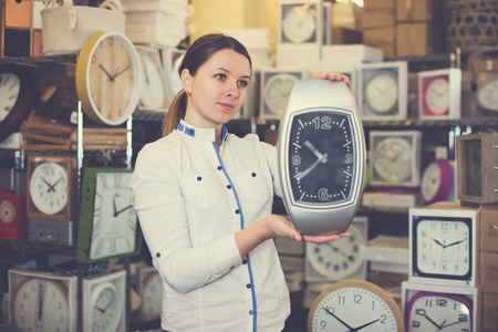 Ordinary woman is standing with modern clock in furniture store