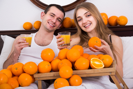 Young russian man and girlfriend drinking squeezed orange juice in bed Stock Photo