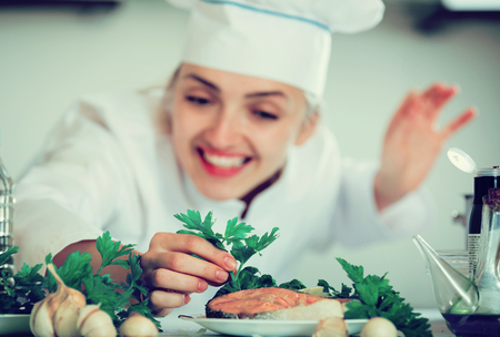 Professional chef with fried salmon fillet in commercial kitchen